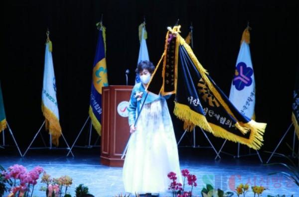 15대 박상춘 서산시여성단체협의회장이 기를 전수받고 흔드는 장면.JPG